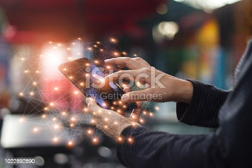 istock Man using mobile smartphone network connection at night on city shopping street. World connected and social networking concept. 1022892890