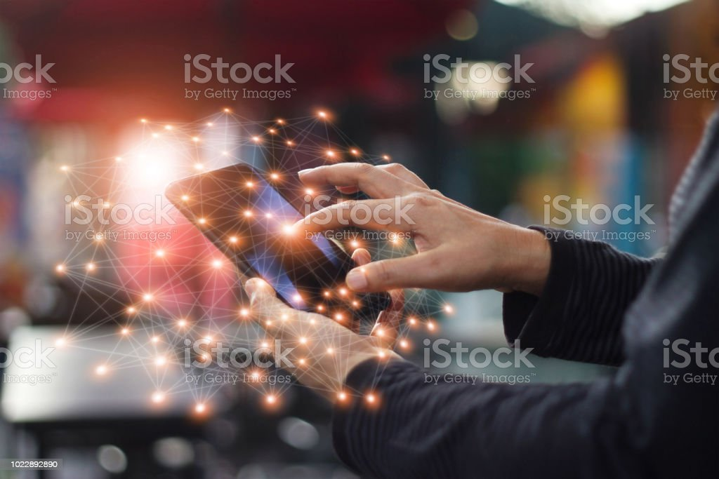 Man using mobile smartphone network connection at night on city shopping street. World connected and social networking concept. - foto stock