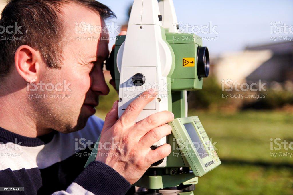 Meu uso de estação total. Agrimensor de cara no trabalho. Levantamento geodésico dispositivo de instrumento, estação total, definido no campo. Trabalhador de topógrafo fazendo a medição no jardim. - foto de acervo