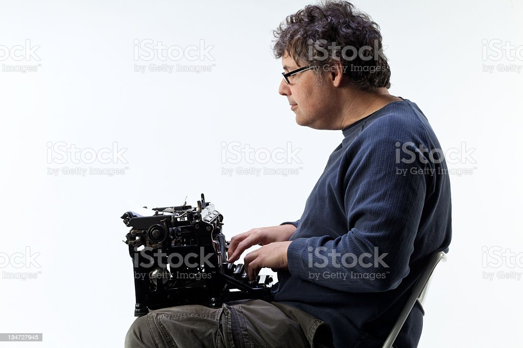 Man using old wireless technology with typewriter in lap royalty-free stock photo