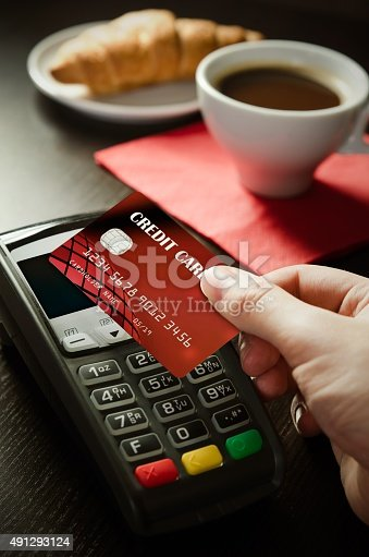 914593772istockphoto Man using payment terminal with NFC technology in cafeteria 491293124