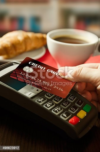 914593772istockphoto Man using payment terminal with NFC technology in cafeteria 495623912