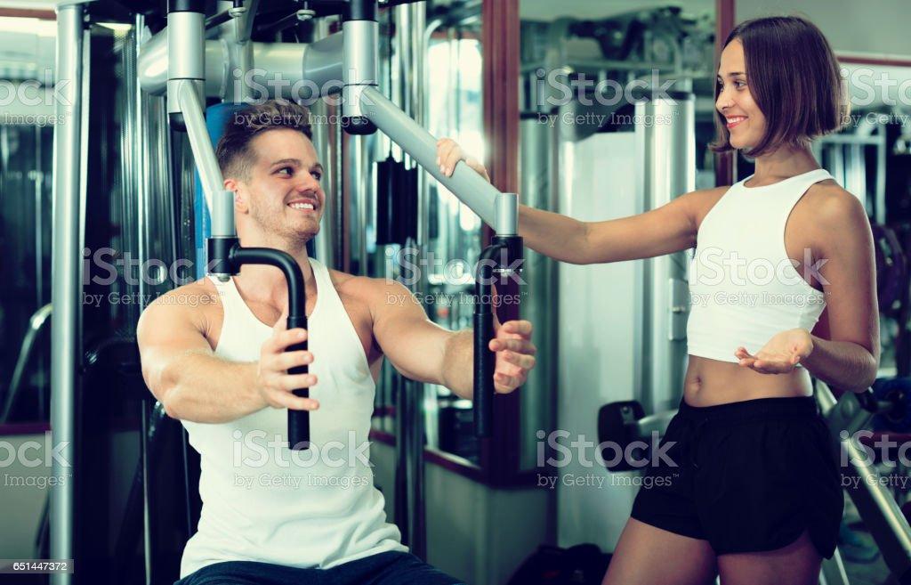 Man using pec deck gym machinery stock photo