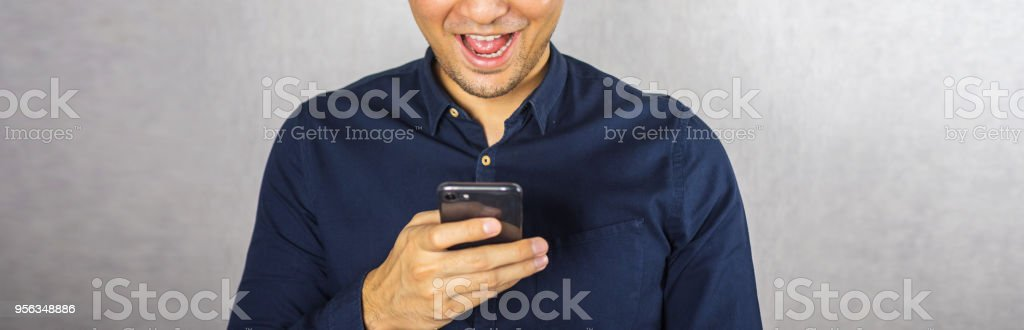 Man using phone and smile on grey background stock photo