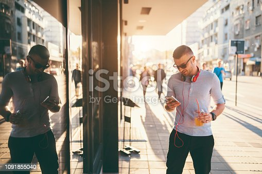Young man listening to music and using phone downtown