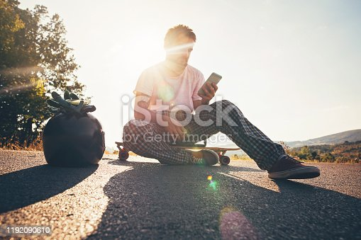 Hipster person sitting on skateboard and text messaging on smart phone
