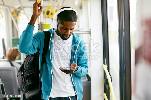 Man Using Phone, Listening Music Traveling In Train. Black Male Student With Headphones Riding In Public Transport. High Resolution