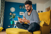 Man sitting home in his armchair and using phone