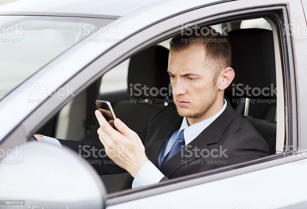 man using phone while driving the car royalty-free stock photo