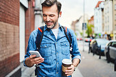 Man using phone with wireless headphones walking in the city and drinking coffee