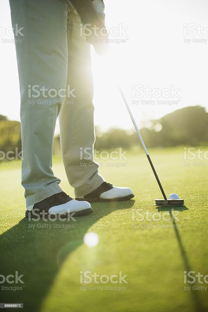 Man using putter to play golf 免版稅 stock photo