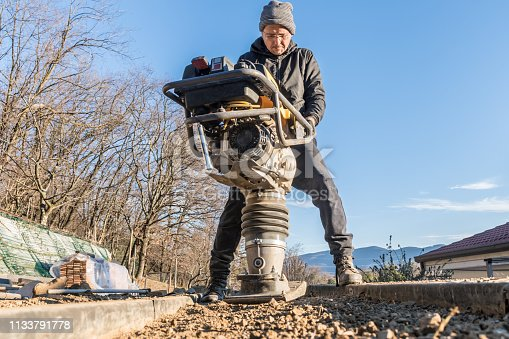 Man Using Rammer Tamper (Jumping Jack) for Soil Compacting