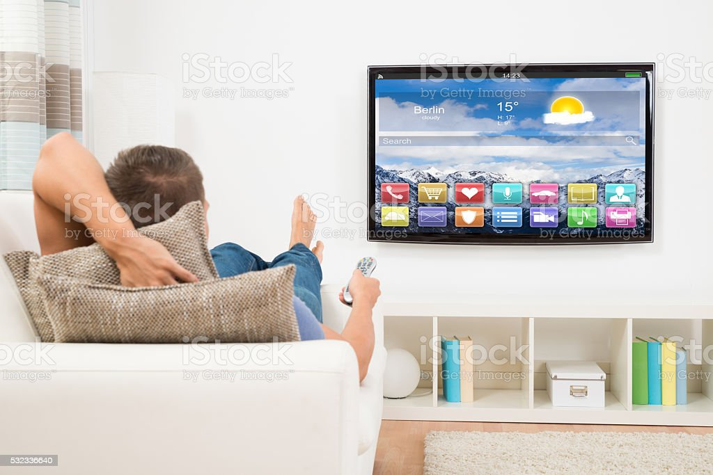 Man Using Remote Control In Front Of Television stock photo