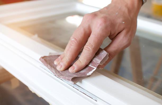 Man using sandpaper on wood window frame stock photo