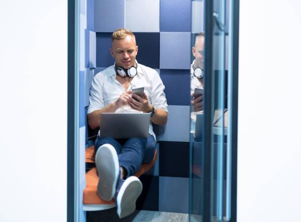 mann mit stillen pod zimmer in modernen co-working office - telefonschrank stock-fotos und bilder