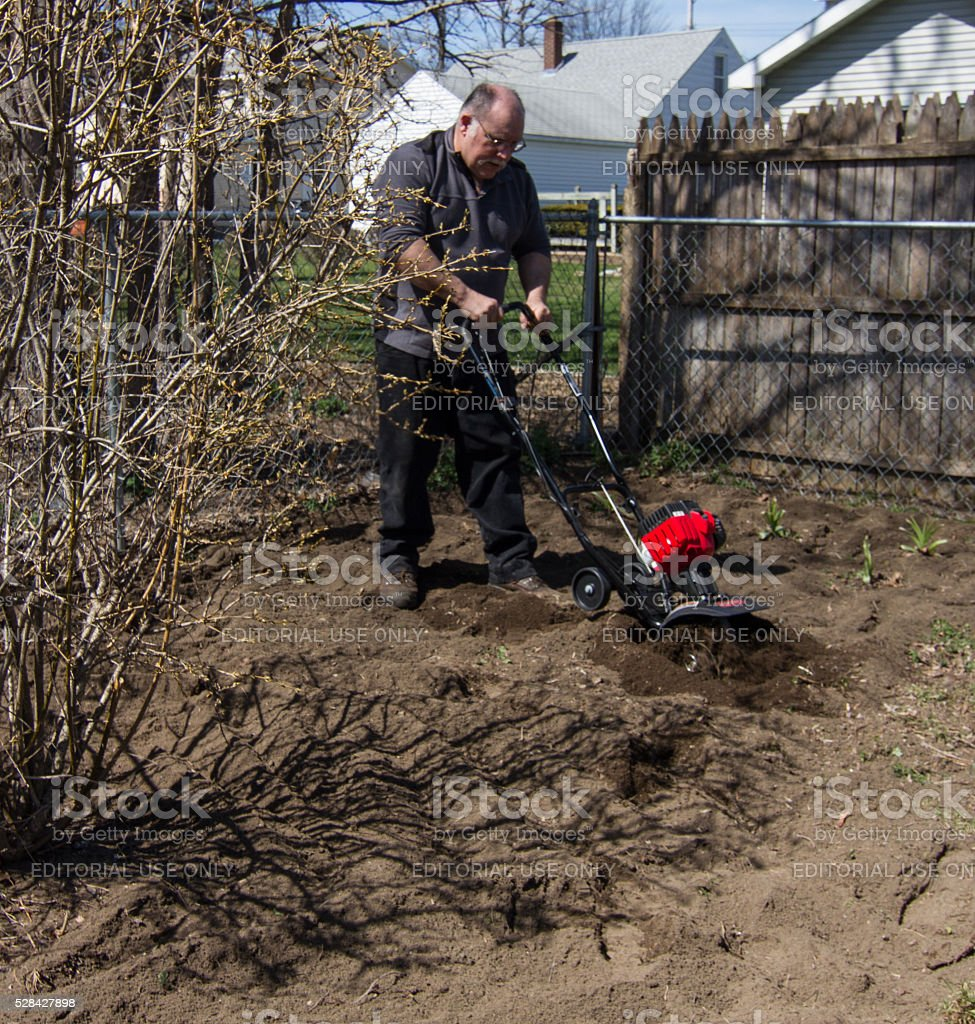 Man using small tiller to loosen soil and prepar garden stock photo