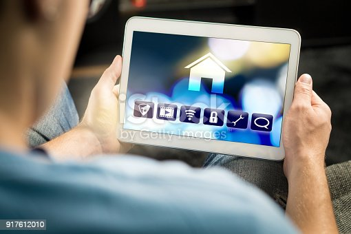 istock Man using smart home application in tablet to control house appliances. Internet of things (IOT) and remote controller app on smart device. 917612010
