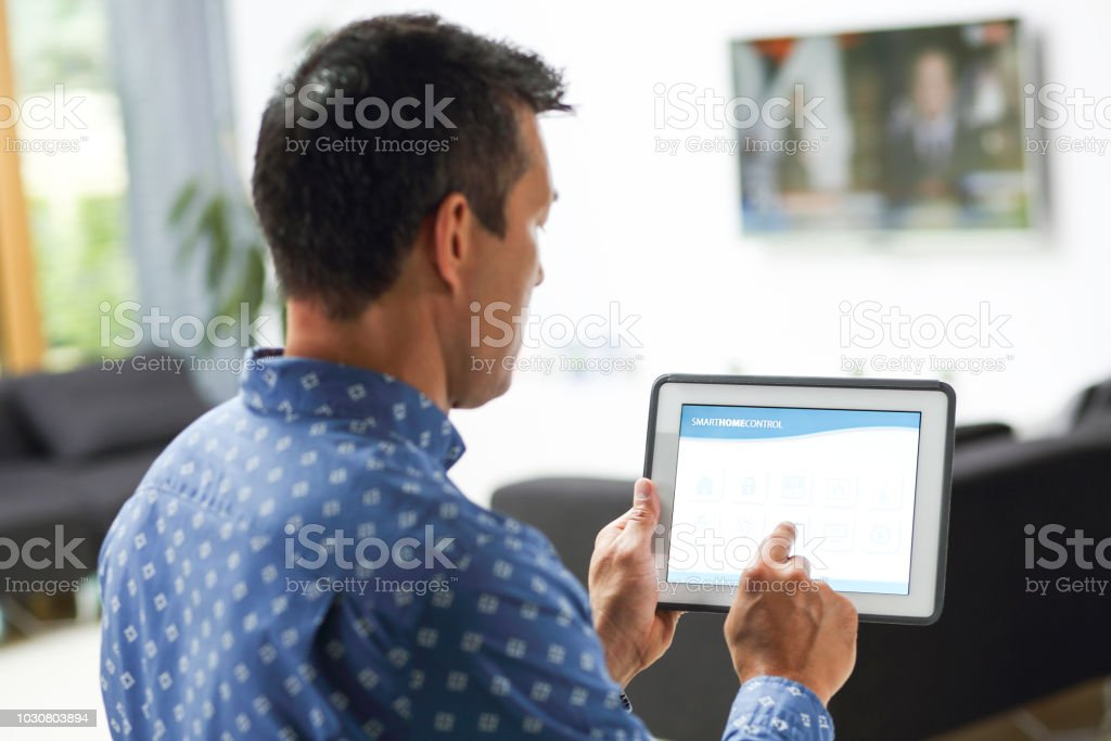 Mid adult man in his home controlling smart home on digital tablet.