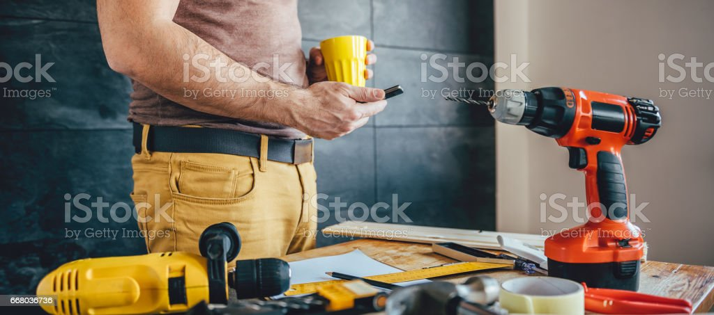 Man using smart phone and holding cup of coffee stock photo