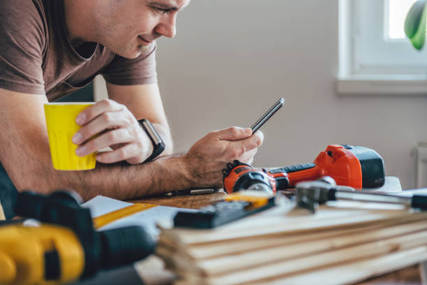 Man using smart phone and holding cup of coffee Man using smart phone and holding yellow cup of coffee in front of table with tools at home craftsperson stock pictures, royalty-free photos & images