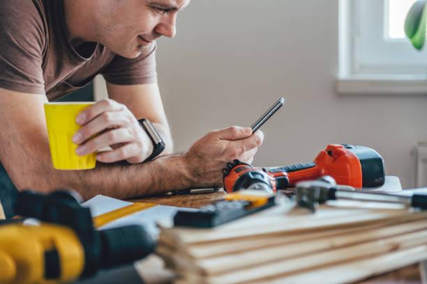 hombre usando el teléfono inteligente y sostener taza de café - obrero de la construcción fotografías e imágenes de stock
