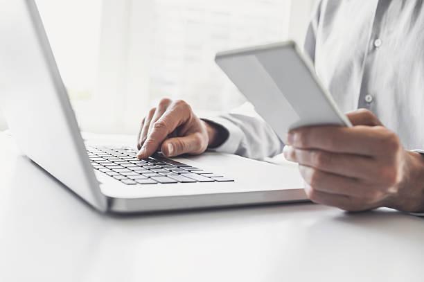 Man using smart phone and laptop - foto de stock