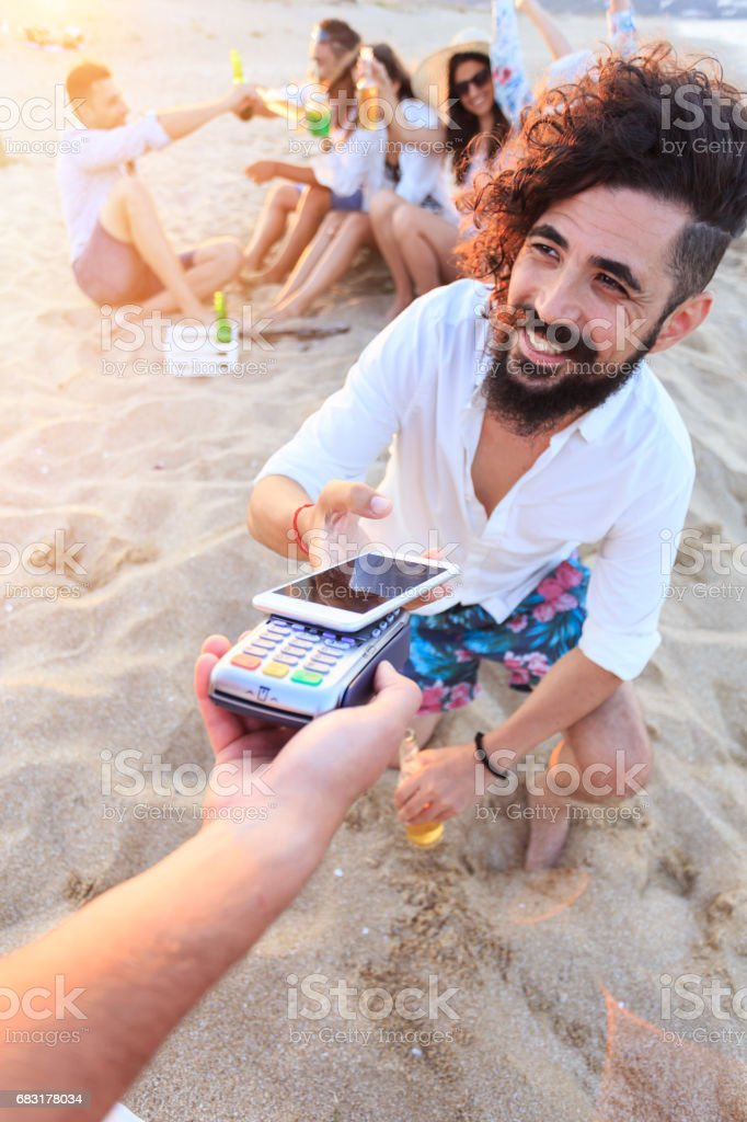 Man using smart phone for contactless payment on beach royalty-free stock photo