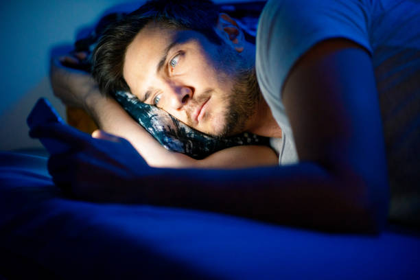 Man using smart phone in bed stock photo