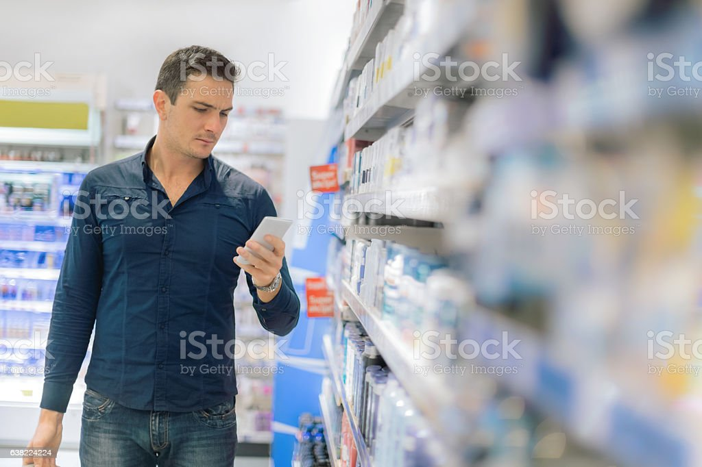 Man using smart phone in supermarket stock photo