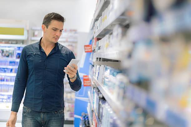 man using smart phone in supermarket - drogerie stock-fotos und bilder