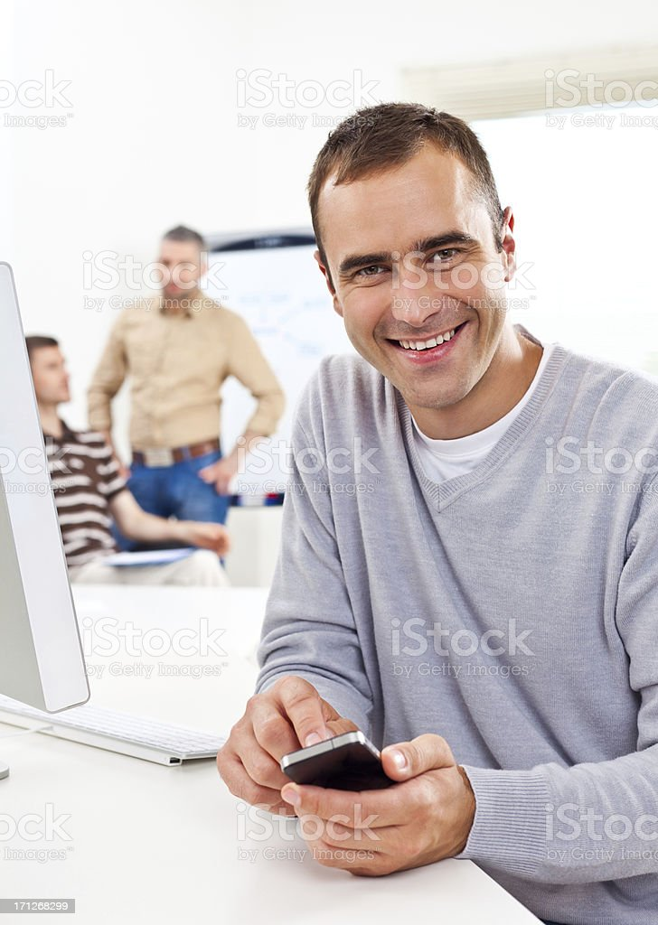 Man using smart phone Smiling man using smart phone in an office, while his colleagues talking in the background. 30-34 Years Stock Photo