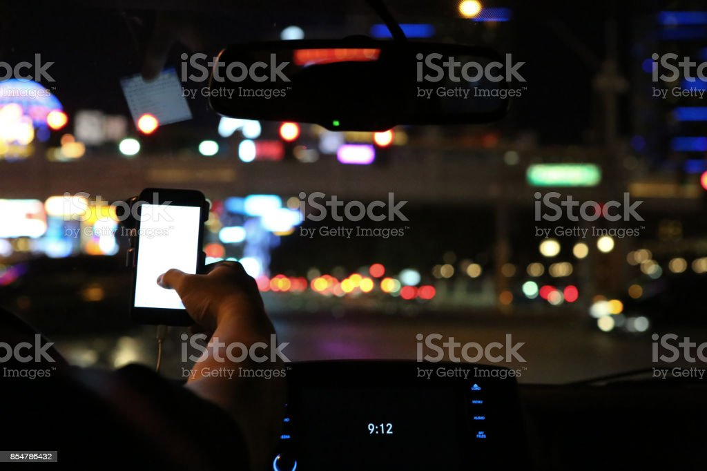 Man using smart phone while driving stock photo