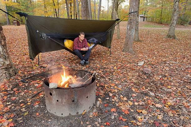 mann mit smartphone während der sitzung in modernen camping hängematte - planenzelt stock-fotos und bilder