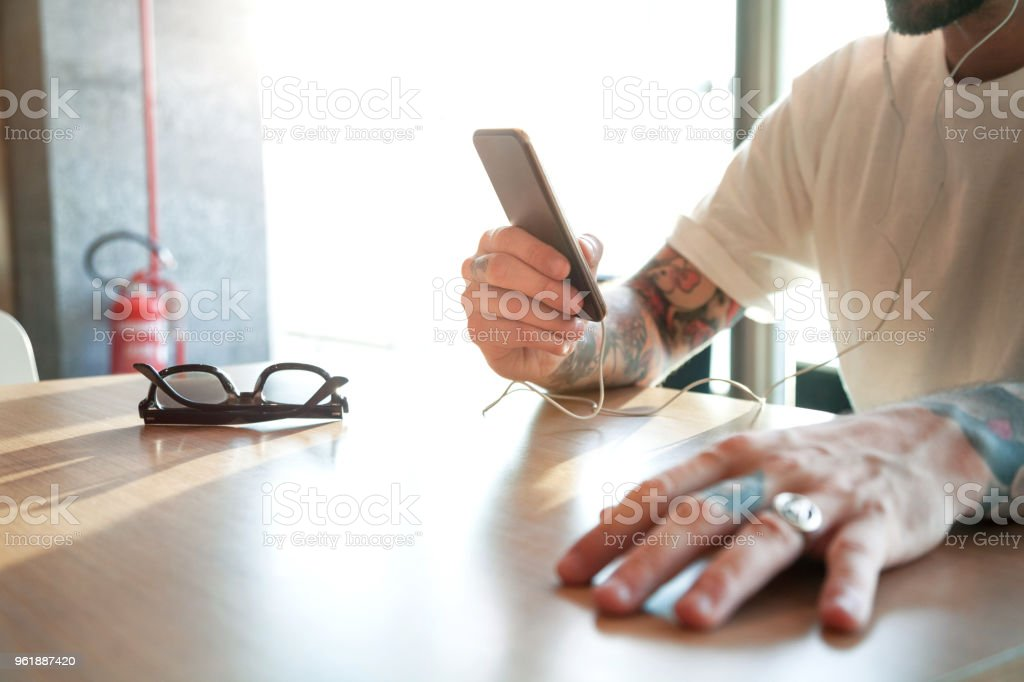 Man using smart phone with ear phones stock photo