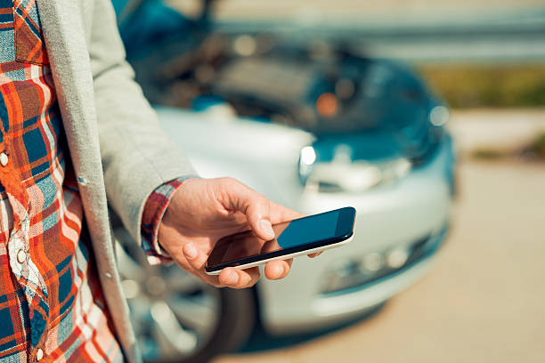 Man using smartphone after traffic accident - foto de stock
