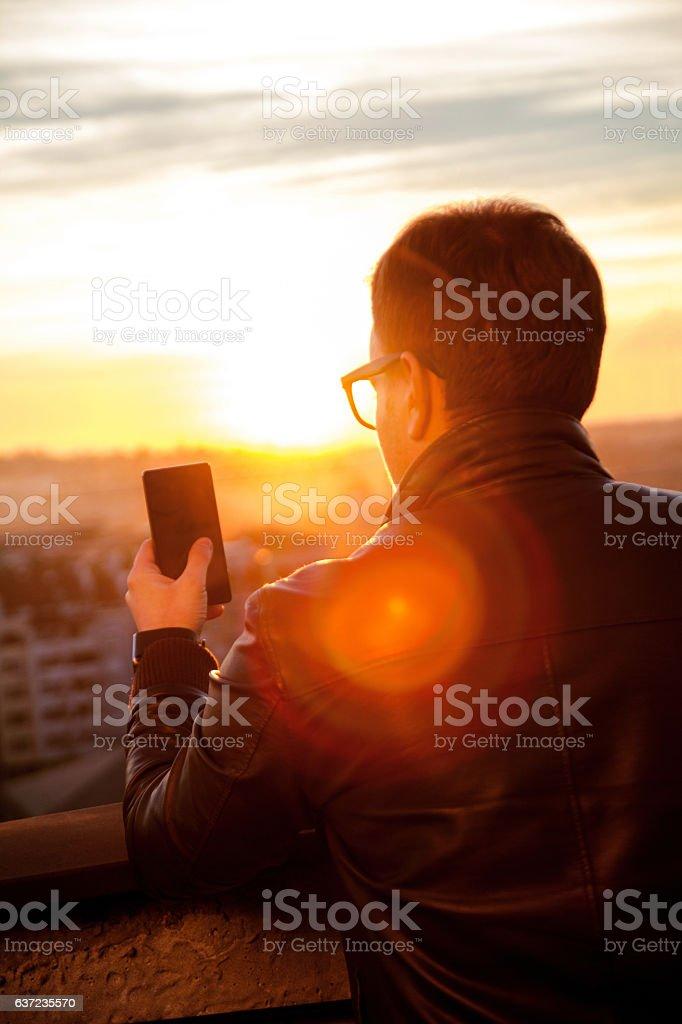 Man using smartphone and taking photos of the city skyline - foto de acervo