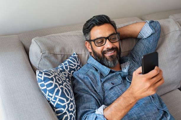 man using smartphone at home - mani dietro la testa foto e immagini stock