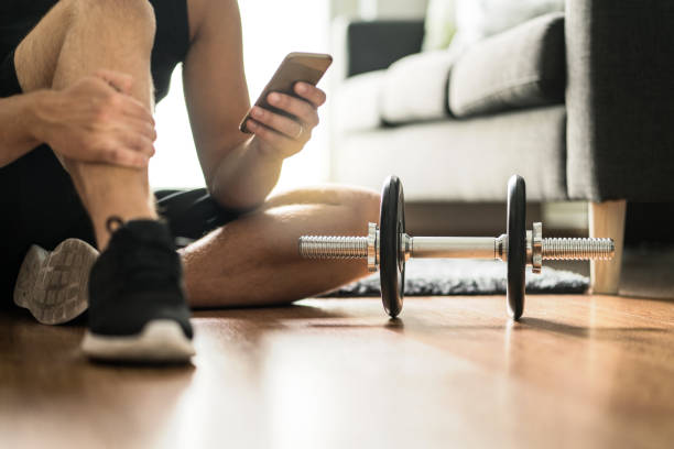 Man using smartphone during workout at home. Online personal trainer or on mobile phone. Internet fitness class or video course. Taking a break. Lazy guy with cellphone while training. stock photo