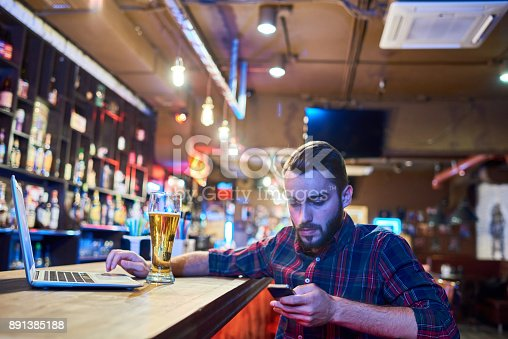 istock Man Using Smartphone in Pub 891385188