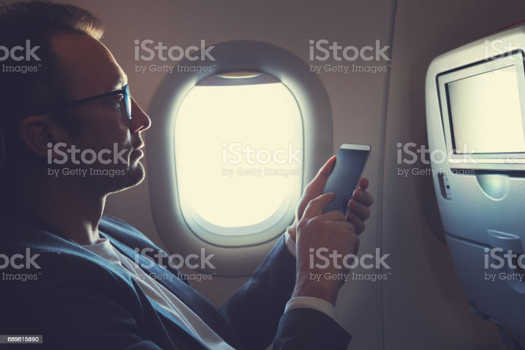 Man using smartphone in the airplane. stock photo