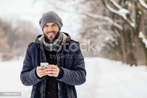 Young man using smartphone on snowy day