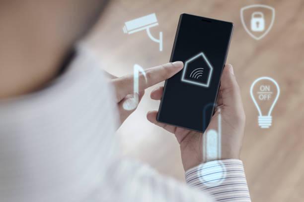 man using smartphone to control smart home - telecomando background foto e immagini stock
