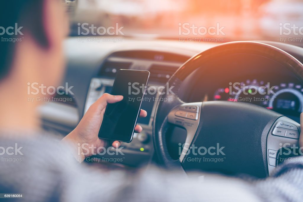 Man using smartphone while driving the car – Foto
