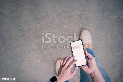 istock man using smartphone while walking on the road 935967348