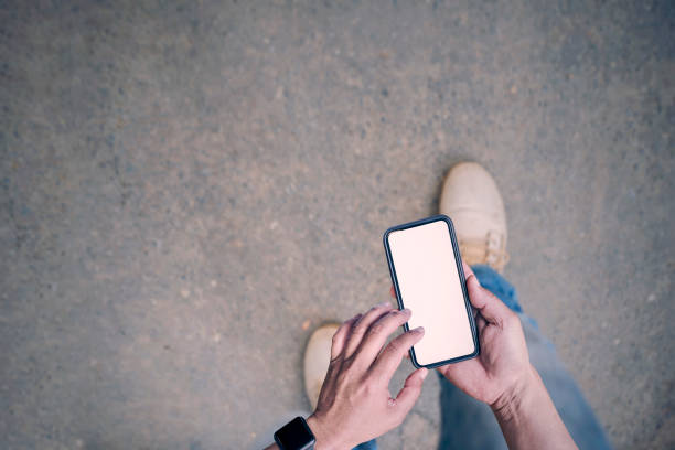 man using smartphone while walking on the road stock photo