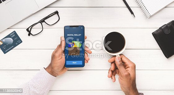 Man using smartphone with digital wallet application, check balance and drinking coffee at workplace, panorama, top view