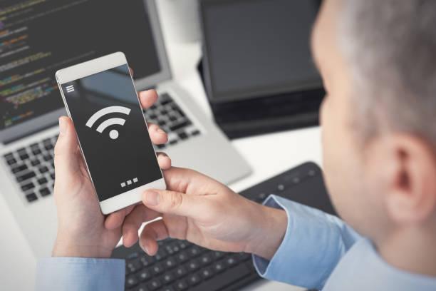 Man using smartphone with wireless symbol stock photo