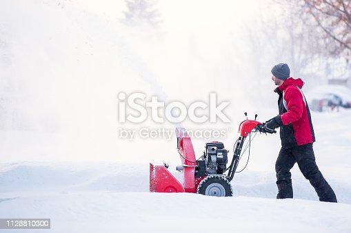 istock Man Using Snow Blower on Winter Day 1128810300