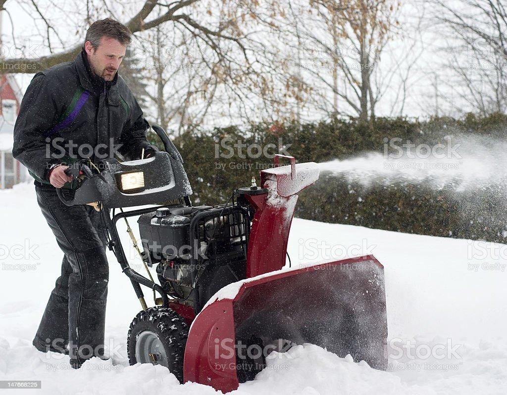 man using snow blower stock photo