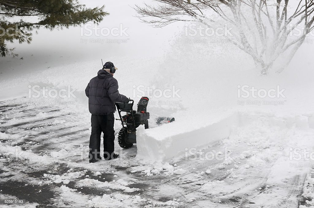 Man Using Snowblower to Clean Driveway stock photo
